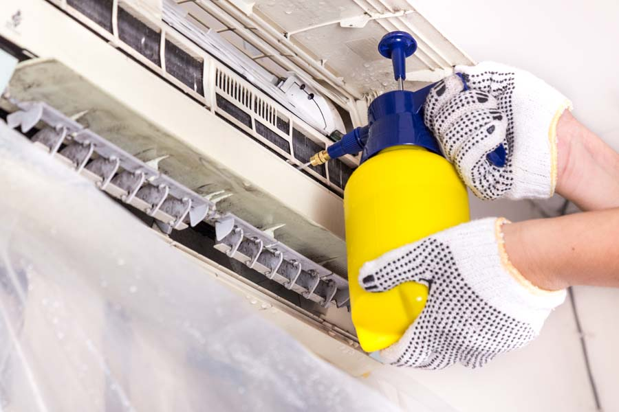 Technician Performing Maintenance and Cleaning on Air Conditioner