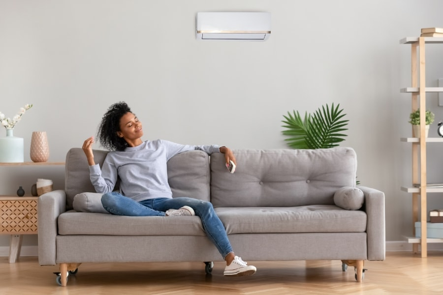 A woman relaxing on a couch | When to Replace Your Entire HVAC System | Round Rock