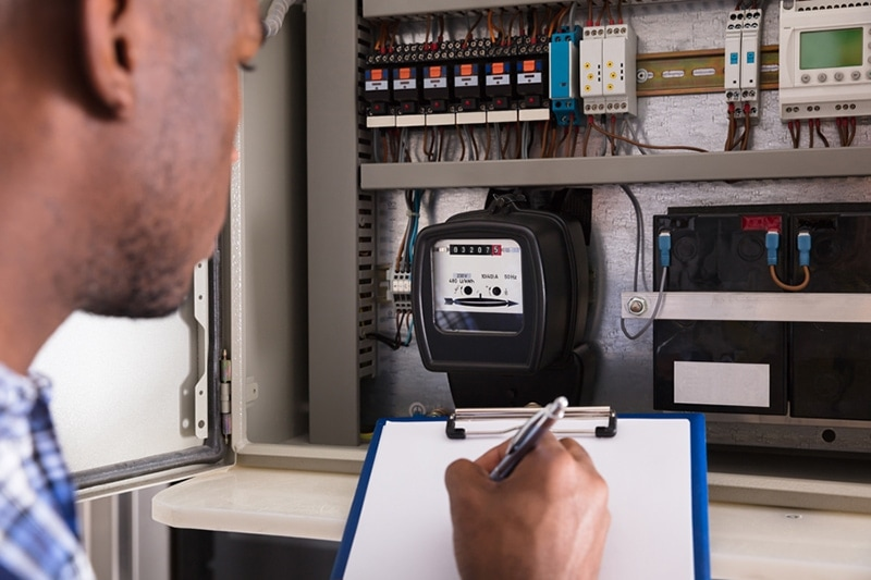 lose-up Of Male Technician Writing On Clipboard In Front Of Fuse Box