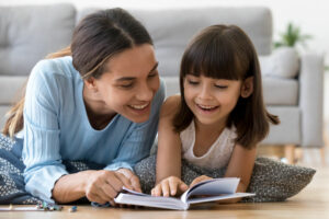 woman and girl read book on floor any season, Should You Install a Zone Control System in Your Home?